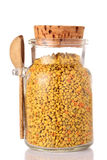 Η γύρη μελισσών σε ένα βάζο γυαλιού καλύπτεται με ένα ξύλινο καπάκι φελλού και ένα ξύλινο κουτάλι σε ένα άσπρο υπόβαθρο Υγιής Στοκ Φωτογραφίες