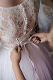 Η γλυκιά όμορφη νύφη φορά ένα μοντέρνο γαμήλιο φόρεμα σε ένα υπόβαθρο Στοκ εικόνα με δικαίωμα ελεύθερης χρήσης