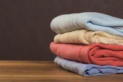 Η δέσμη των πλεκτών θερμών πουλόβερ με τα διαφορετικά πλέκοντας σχέδια δίπλωσε στο σωρό στον καφετή ξύλινο πίνακα στοκ εικόνα με δικαίωμα ελεύθερης χρήσης