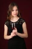 Η Δεσποινίς στο ποτήρι εκμετάλλευσης φορεμάτων του κρασιού κλείστε επάνω ανασκόπηση σκούρο κόκκιν&omi Στοκ Εικόνα