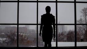 Η δημιουργική επιχειρησιακή γυναίκα έρχεται στο παράθυρο στο γραφείο απόθεμα βίντεο