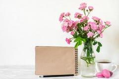 Η δημιουργική χλεύη επάνω με μια όμορφη ανθοδέσμη των ρόδινων τριαντάφυλλων ανθίζει, φλυτζάνι καφέ, macaroons και κενό σημειωματά Στοκ Φωτογραφίες