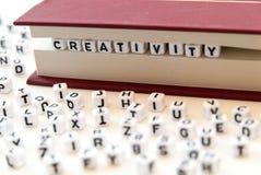 Η δημιουργικότητα λέξης που γράφτηκε με τις επιστολές μεταξύ ενός άσπρου υποβάθρου σελίδων βιβλίων με τις επιστολές διέδωσε γύρω  Στοκ Φωτογραφίες