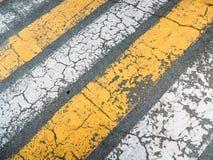 Η διαγώνιος ράγισε τις κίτρινες και άσπρες γραμμές χρωμάτων στην γκρίζα οδική σύσταση ασφάλτου, τη τοπ άποψη ως grunge υπόβαθρο ή Στοκ φωτογραφίες με δικαίωμα ελεύθερης χρήσης