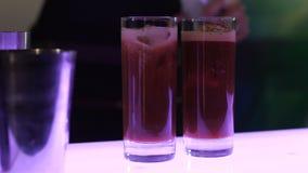 Η διαδικασία ένα κοκτέιλ, ο μπάρμαν σε δύο γυαλιά με ένα μαγειρευμένο κοκτέιλ με τον πάγο ολοκληρώνει το δηλητηριασμένο με αέρια  φιλμ μικρού μήκους