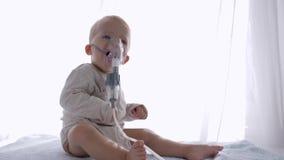 Η διαδικασία εισπνοής, καλό αγόρι μικρών παιδιών αναπνέει μέσω nebulizers για την ανάφλεξη απολαύσεων των εναέριων διαδρόμων στο  απόθεμα βίντεο