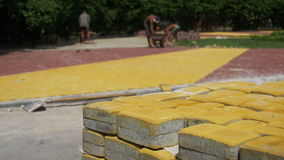 Η διαδικασία οικοδόμησης, που επισκευάζει το πεζοδρόμιο Εργαζόμενος που βάζει την πέτρινη επίστρωση σε ένα πάρκο πόλεων φιλμ μικρού μήκους