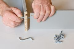 Η διαδικασία του κατεβατού δύο τοίχοι του κιβωτίου κουζινών κατά τη συγκέντρωση των επίπλων Μια από τις βίδες σφίγγεται ήδη, ο δε στοκ φωτογραφίες με δικαίωμα ελεύθερης χρήσης