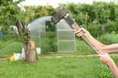 Η διαδικασία το ξύλο με έναν μπαλτά Το άτομο κρατά ένα τσεκούρι στοκ εικόνα με δικαίωμα ελεύθερης χρήσης