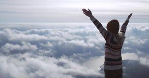Η διακινούμενη επιτυχία γυναικών αύξησε τα χέρια απολαμβάνοντας το τοπίο πέρα από τα σύννεφα στην έννοια τρόπου ζωής κορυφών βουν φιλμ μικρού μήκους