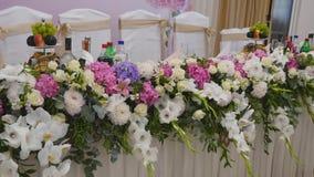 Η διακόσμηση γαμήλιων πινάκων με τα λουλούδια, γαμήλιος πίνακας διακοσμήσεων λουλουδιών, γαμήλιος ανθοκόμος, γάμος στον πίνακα εί απόθεμα βίντεο