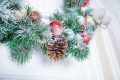 Η διακόσμηση εγχώριων Χριστουγέννων στον άσπρο τοίχο, έλατο διακλαδίζεται, γιρλάντα και pinecone, αριθμός αγγέλου, κάρτα Χριστουγ στοκ φωτογραφία με δικαίωμα ελεύθερης χρήσης