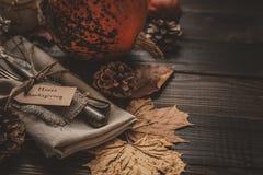 Η διακόσμηση ημέρας των ευχαριστιών με τα μαχαιροπήρουνα και η πετσέτα στον ξύλινο πίνακα, κλείνουν επάνω Στοκ Εικόνα