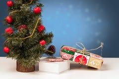 Η διακόσμηση Χριστουγέννων σε ένα μπλε θολωμένο υπόβαθρο με παρουσιάζει Στοκ Εικόνες