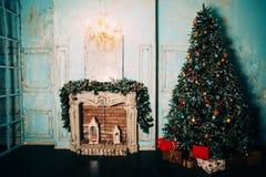 Η διακόσμηση Χριστουγέννων στο εσωτερικό δωματίων grunge με την εστία, λικνίζοντας καρέκλα παιδιών αλόγων, κλασικό νέο δέντρο έτο στοκ εικόνες