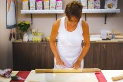 Η διδακτική γυναίκα επιδεικνύει πώς στο sfoglia ` Λα τιμής ` κάνοντας το sfoglia ζυμαρικών για τα φρέσκα σπιτικά ζυμαρικά με την  Στοκ Εικόνα