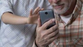Η διδασκαλία εγγονών granddad για να χρησιμοποιήσει την εφαρμογή smartphone, παρουσίαση φυλλομετρεί επάνω απόθεμα βίντεο