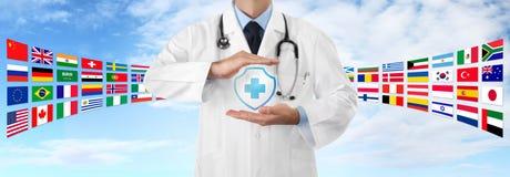 Η διεθνής έννοια ιατρικής ασφάλειας ταξιδιού, χέρια του γιατρού προστατεύει ένα διαγώνιο εικονίδιο ασπίδων, στο υπόβαθρο μπλε ουρ στοκ φωτογραφίες