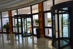 Η δομή τρεις-πορτών οικοδόμησης εμπορικών κέντρων πορτών γυαλιού έδεσε την περιστροφή σε έναν κάθετο άξονα και ένα πορτοκαλί υγρό στοκ φωτογραφία