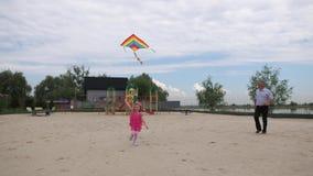 Η εγγονή και ο παππούς προωθούν έναν ικτίνο αέρα στην παραλία Τρέχουν και χαμογελούν r απόθεμα βίντεο