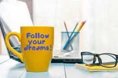 Η εγγραφή του εμπνευσμένου αποσπάσματος ακολουθεί τα όνειρά σας στον κίτρινο καφέ πρωινού ή άλλο καυτό φλυτζάνι ποτών στο σπίτι,  Στοκ Εικόνες