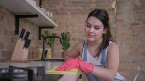 Η εγχώρια βελτίωση, όμορφη νοικοκυρά γυναικών στα λαστιχένια γάντια για τον καθαρισμό σκουπίζει τα σκονισμένα έπιπλα στην κουζίνα φιλμ μικρού μήκους