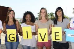 Η εθελοντική ομάδα με το σημάδι δίνει στοκ εικόνα
