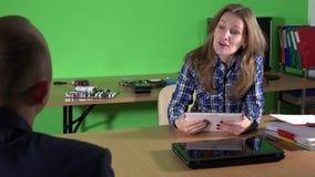 Η ειδικευμένη γυναίκα επιδιορθωτών υπολογιστών με τα πόδια στο γραφείο συναντά τον πελάτη με το lap-top φιλμ μικρού μήκους