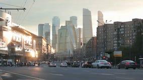 Η εικονική παράσταση πόλης στο ηλιοβασίλεμα με την κυκλοφορία αυτοκινήτων πόλεων σταμάτησε σε έναν κόκκινο φωτεινό σηματοδότη στο απόθεμα βίντεο