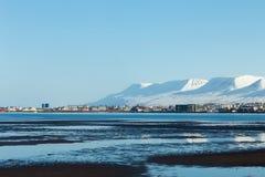 Η εικονική παράσταση πόλης της Ισλανδίας πέρα από seacoast με παρουσιάζει καλυμμένο βουνό Στοκ εικόνες με δικαίωμα ελεύθερης χρήσης