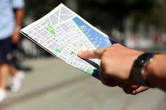 Η εικόνα ενός στενού επάνω ατόμου ψάχνει τις κατευθύνσεις στο χάρτη έξω στοκ φωτογραφία με δικαίωμα ελεύθερης χρήσης