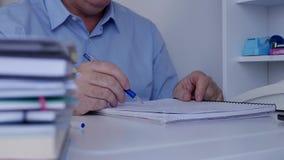 Η εικόνα με τον επιχειρηματία δίνει το σχεδιασμό γραψίματος και υπολογισμός χρησιμοποιώντας Copybook απόθεμα βίντεο