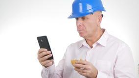 Η εικόνα μηχανικών τρώει ένα σάντουιτς και ένα κείμενο χρησιμοποιώντας το κινητό τηλέφωνο στοκ φωτογραφία με δικαίωμα ελεύθερης χρήσης
