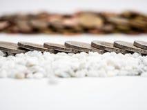 Η εικόνα της γραμμής δύο ευρο- νομισμάτων στις άσπρες μικρές πέτρες κλείνει επάνω στοκ φωτογραφία