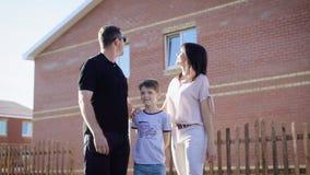 Η εικόνα της ευτυχούς οικογένειας έντυσε στα περιστασιακά ενδύματα που στέκονται κοντά στο καινούργιο σπίτι τους στην ηλιόλουστη  απόθεμα βίντεο