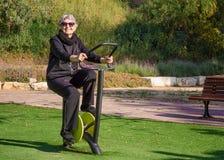 Η εικόνα της ηλικιωμένης γυναίκας δένει τον έξω περιστρεφόμενο εκπαιδευτή κύκλων Στοκ φωτογραφίες με δικαίωμα ελεύθερης χρήσης