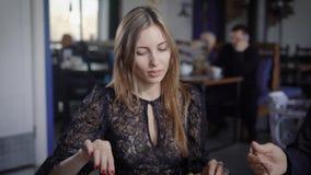 Η εικόνα της νέας όμορφης γυναίκας έντυσε στα μαύρα τρόφιμα κατανάλωσης και το χρόνο εξόδων με το φίλο της Ζεύγος των φίλων απόθεμα βίντεο