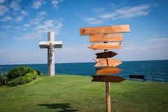 Η εικόνα της ξύλινης κατεύθυνσης καθοδηγεί μπροστά από τη θάλασσα και τη χλόη Στοκ Εικόνα