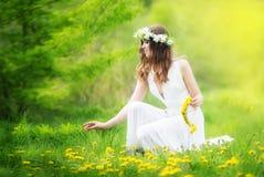 Η εικόνα της όμορφης γυναίκας σε ένα άσπρο φόρεμα υφαίνει τη γιρλάντα από το dande Στοκ Φωτογραφία