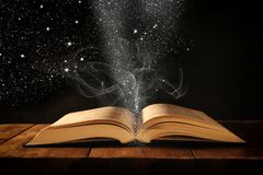 η εικόνα του ανοικτού παλαιού βιβλίου στον ξύλινο πίνακα με ακτινοβολεί επικάλυψη Στοκ Εικόνες