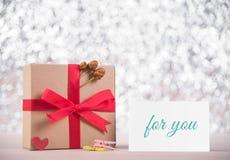 Η εικόνα του κιβωτίου δώρων με την κόκκινη κορδέλλα και το μήνυμα σας αγαπούν στο gree Στοκ Εικόνες