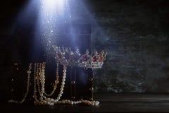 Η εικόνα του μυστήριου ανοιγμένου παλαιού ξύλινου στήθους θησαυρών με το φως και τη βασίλισσα/ο βασιλιάς στέφει με τις κόκκινες π Στοκ Φωτογραφίες