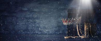 Η εικόνα του μυστήριου ανοιγμένου παλαιού ξύλινου στήθους θησαυρών με το φως και τη βασίλισσα/ο βασιλιάς στέφει με τις κόκκινες π Στοκ Εικόνα