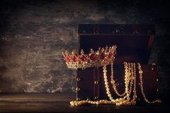 Η εικόνα του μυστήριου ανοιγμένου παλαιού ξύλινου στήθους θησαυρών με το φως και τη βασίλισσα/ο βασιλιάς στέφει με τις κόκκινες π Στοκ Φωτογραφία