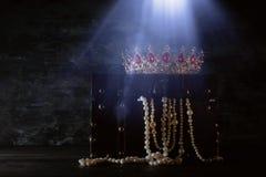 Η εικόνα του μυστήριου ανοιγμένου παλαιού ξύλινου στήθους θησαυρών με το φως και τη βασίλισσα/ο βασιλιάς στέφει με τις κόκκινες π Στοκ φωτογραφία με δικαίωμα ελεύθερης χρήσης