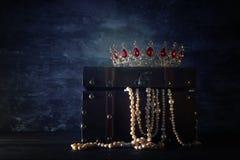 Η εικόνα του μυστήριων ανοιγμένων παλαιών ξύλινων στήθους και της βασίλισσας θησαυρών/ο βασιλιάς στέφει με τις κόκκινες πέτρες ρο Στοκ Εικόνα
