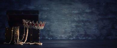 Η εικόνα του μυστήριων ανοιγμένων παλαιών ξύλινων στήθους και της βασίλισσας θησαυρών/ο βασιλιάς στέφει με τις κόκκινες πέτρες ρο Στοκ Φωτογραφίες