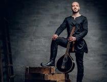 Η εικόνα των αρσενικών μουσικών στα παλαιά παραδοσιακά κελτικά ενδύματα κρατά το εκλεκτής ποιότητας μαντολίνο Στοκ Φωτογραφία