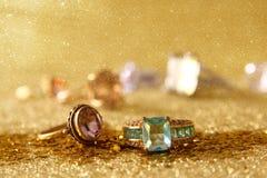 Η εικόνα των κομψών χρυσών δαχτυλιδιών στο χρυσό ακτινοβολεί υπόβαθρο Στοκ εικόνα με δικαίωμα ελεύθερης χρήσης