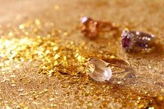 Η εικόνα των κομψών χρυσών δαχτυλιδιών στο χρυσό ακτινοβολεί υπόβαθρο Στοκ Φωτογραφία